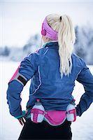 Rear view of woman wearing water bottle belt listening music in winter Stock Photo - Premium Royalty-Freenull, Code: 698-06804099