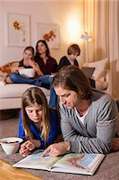 Father and daughter reading map on floor with family sitting on sofa in background Stock Photo - Premium Royalty-Freenull, Code: 698-06804161