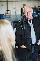 Senior male customer discussing with female mechanic at workshop Stock Photo - Premium Royalty-Freenull, Code: 698-06804327