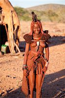 Young Himba woman wearing traditional dress and jewellery and with her skin covered in Otjize, a mixture of butterfat and ochre, Kunene Region, formerly Kaokoland, Namibia, Africa Stock Photo - Premium Rights-Managednull, Code: 841-06805770