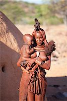 Young Himba woman, with baby, wearing traditional dress and jewellery and with her skin covered in Otjize, a mixture of butterfat and ochre, Kunene Region, formerly Kaokoland, Namibia, Africa Stock Photo - Premium Rights-Managednull, Code: 841-06805772