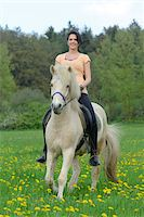 Young woman riding a icelandic horse on a meadow in spring, Germany Stock Photo - Premium Rights-Managednull, Code: 700-06808856
