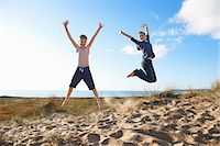 Boy and teenage girl jumping on beach Stock Photo - Premium Royalty-Freenull, Code: 649-06812049
