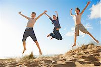 Boys and teenage girl jumping on beach Stock Photo - Premium Royalty-Freenull, Code: 649-06812050