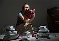 Girl sitting on pile of books reading Stock Photo - Premium Royalty-Freenull, Code: 649-06812225