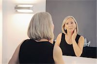 Senior woman looking at reflection in mirror Stock Photo - Premium Royalty-Freenull, Code: 649-06812370