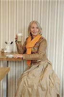 Senior woman sitting on coffee shop Stock Photo - Premium Royalty-Freenull, Code: 649-06812376