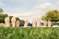 Family with two children lying on grass, focus on feet Stock