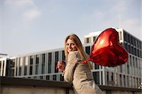 Woman with red heart-shaped balloon Stock Photo - Premium Royalty-Freenull, Code: 649-06813029