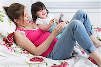 expectation - Portrait of pregnant woman and toddler daughter lounging on bed playing with smartphone Stock Photo - Premium Royalty-Freenull, Code: 614-06813761
