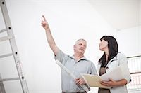 Male and female  talking and pointing upwards holding  blueprints next to ladders Stock Photo - Premium Royalty-Freenull, Code: 614-06813847