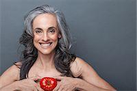 Mature woman holding red tomato Stock Photo - Premium Royalty-Freenull, Code: 614-06814173
