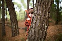 Male toddler wearing tiger suit hiding behind tree Stock Photo - Premium Royalty-Freenull, Code: 614-06814352