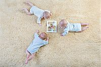 Three babies look at a picture of themselves on a digital tablet Stock Photo - Premium Royalty-Freenull, Code: 653-06819487