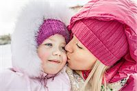 A mother kissing her daughter outdoors in winter Stock Photo - Premium Royalty-Freenull, Code: 653-06819644