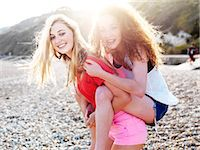 A young woman giving her teenage friend a piggyback ride at the beach Stock Photo - Premium Royalty-Freenull, Code: 653-06819727