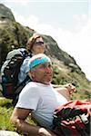 Close-up of mature couple sitting on grass, hiking in mountains, Tannheim Valley, Austria