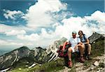 Mature couple sitting on grass, hiking in mountains, Tannheim Valley, Austria