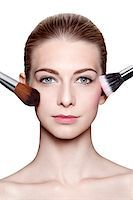 Close-Up of Young Woman Applying Make-Up with Brushes on White Background Stock Photo - Premium Rights-Managednull, Code: 700-06826407