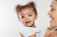 Young woman holding baby daughter in studio Stock Photo - Premium Royalty-Freenull, Code: 649-06829438