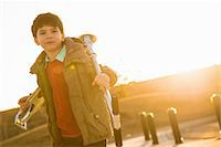 Boy in park carrying scooter Stock Photo - Premium Royalty-Freenull, Code: 649-06829863