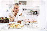 Portrait of woman with selection of hand made cakes Stock Photo - Premium Royalty-Freenull, Code: 649-06830180
