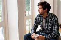 man looking out of window holding a mug Stock Photo - Premium Royalty-Freenull, Code: 6106-06831645