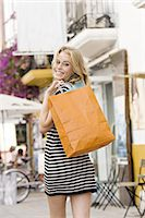 Youn woman in street holding bags Stock Photo - Premium Rights-Managednull, Code: 877-06832532