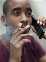 Teenage boy smoking while phoning Stock Photo - Premium Rights-Managednull, Code: 877-06833930