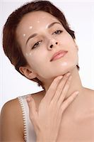 Portrait of a young brunette woman spreading cream on neck Stock Photo - Premium Rights-Managednull, Code: 877-06836381