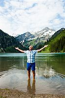 Mature man with arms stretched outward, standing in Lake Vilsalpsee, Tannheim Valley, Austria Stock Photo - Premium Royalty-Freenull, Code: 600-06841891