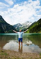 Mature man with arms stretched outward, standing in Lake Vilsalpsee, Tannheim Valley, Austria Stock Photo - Premium Royalty-Freenull, Code: 600-06841892