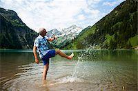 Mature man standing in lake, kicking water, Lake Vilsalpsee, Tannheim Valley, Austria Stock Photo - Premium Royalty-Freenull, Code: 600-06841894
