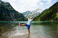 Mature man standing in lake, kicking water, Lake Vilsalpsee, Tannheim Valley, Austria Stock Photo - Premium Royalty-Freenull, Code: 600-06841895