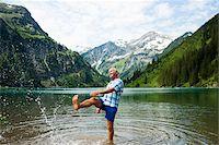 Mature man standing in lake, kicking water, Lake Vilsalpsee, Tannheim Valley, Austria Stock Photo - Premium Royalty-Freenull, Code: 600-06841896