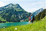 Mature man and woman looking at scenic view, Lake Vilsalpsee, Tannheim Valley, Austria