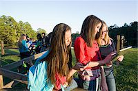 Group of pre-teens sitting on fence, looking at tablet computers and cellphones, outdoors, Florida, USA Stock Photo - Premium Royalty-Freenull, Code: 600-06841922