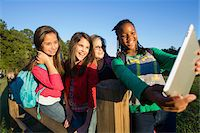 Pre-teen girls standing outdoors, looking at tablet computer laughing, Florida, USA Stock Photo - Premium Royalty-Freenull, Code: 600-06841923