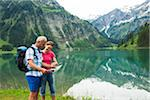 Mature couple looking at map, hiking in mountains, Lake Vilsalpsee, Tannheim Valley, Austria