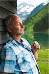Portrait of mature man with eyes closed, holding flower, standing next to building at Lake Vilsalpsee, Tannheim Valley, Austria