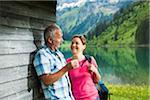 Mature man offering flower to mature woman, standing next to building at Lake Vilsalpsee, Tannheim Valley, Austria