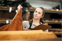 Worker looking at roll of leather Stock Photo - Premium Royalty-Freenull, Code: 649-06844101