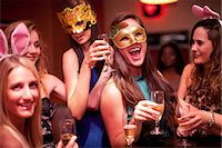 Young women with drinks wearing masks at hen party Stock Photo - Premium Royalty-Freenull, Code: 649-06844379