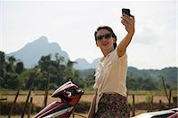 Woman photographing self on moped, Vang Vieng, Laos Stock Photo - Premium