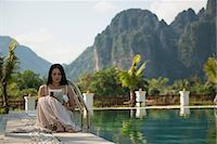 exotic outdoors - Woman sitting reading by swimming pool, Vang Vieng, Laos Stock Photo - Premium Royalty-Freenull, Code: 649-06844482