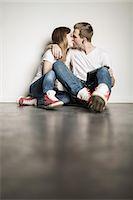 Teenage couple sitting on floor kissing Stock Photo - Premium Royalty-Freenull, Code: 649-06844573