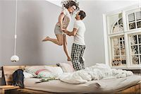 Mid adult couple wearing pyjamas jumping on bed Stock Photo - Premium Royalty-Freenull, Code: 649-06844748