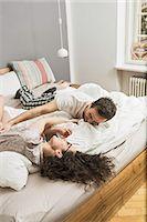 Mid adult couple wearing pyjamas lying on bed tickling Stock Photo - Premium Royalty-Freenull, Code: 649-06844751