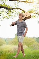 Young man walking through field with guitar Stock Photo - Premium Royalty-Freenull, Code: 649-06845148