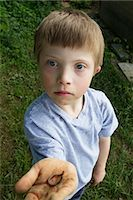 Close up portrait of boy with a worm in his hand Stock Photo - Premium Royalty-Freenull, Code: 649-06845253